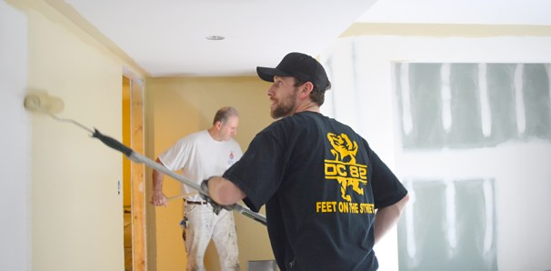 Jordan Fry (front) of Painters Local 61 and Alan Legan of Local 386 finish the home's basement walls.