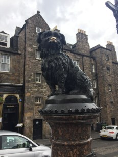 This is a statue of Greyfriars Bobby, a little pup who kept vigil by his master's grave in Greyfriars cemetery. The dog is now buried alongside his owner. Bobby even has a pub named after him right behind this statue.