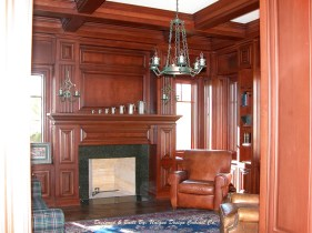 Traditional cherry wood library cabinetry with matching ceiling beams and mantel