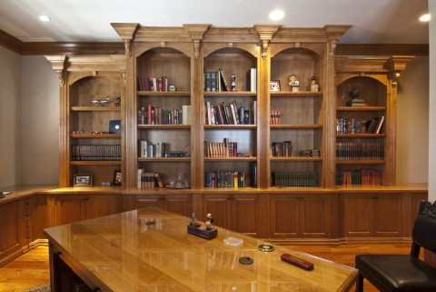 Alder wood office cabinetry with detailed crown and glass covered counter tops