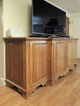Quarter-sawn oak TV base with flush-hung doors; carved posts; carved feet. LED illuminated interior.