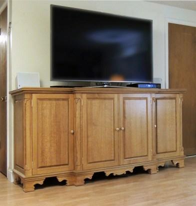 Quarter-sawn oak TV base with flush-hung doors; carved posts; carved feet. LED illuminated interior.