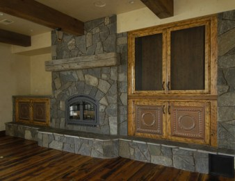 Faux antiqued alder finished to emulate old barn wood. Oil rubbed bronze wire mesh on the TV doors. Tin ceiling panels on the lower doors.