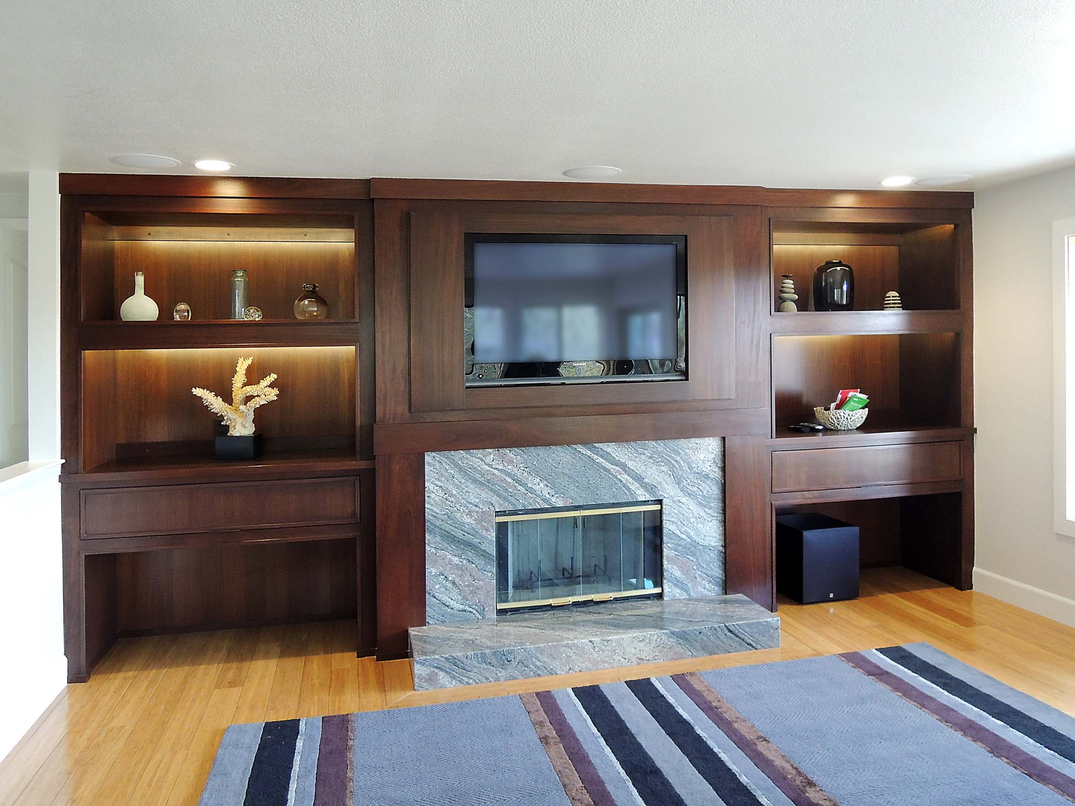 Mahogany Niche Inset Cabinets With LED Illumination And Framed In TV.  Fireplace Surround With Granite