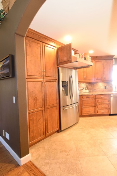 Full overlay maple wood cabinets with extra large roll out above the fridge