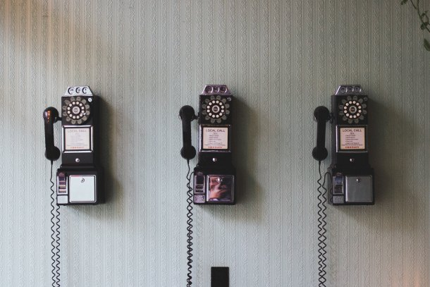 Three retro, rotary pay phones hanging on a wall
