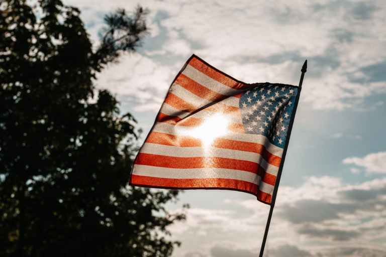 american flag under a cloudy sky