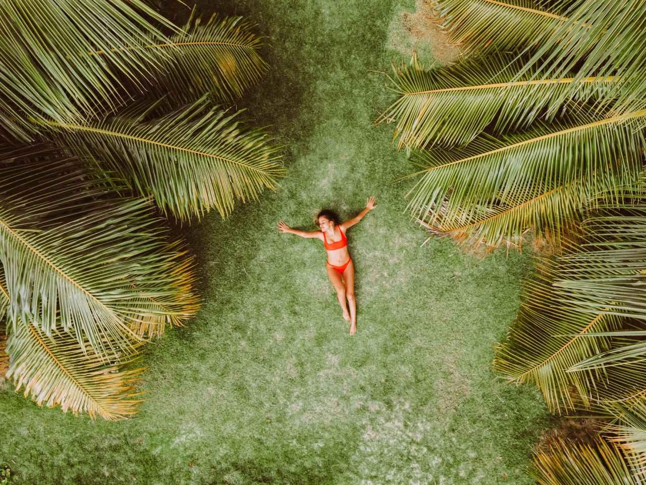 woman lying on green grass among palms at resort