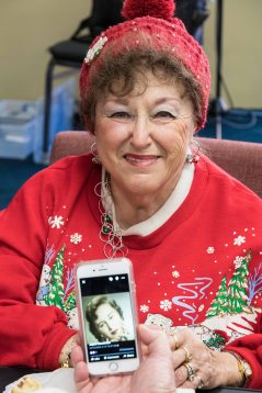 Joyce the Elf, with a photo of herself on the phone