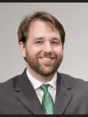Portrait of bearded white man in a suit with green tie.