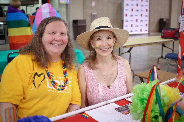 Two people wearing rainbow gear sitting at a table