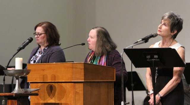 Three women at a pulpit speaking into microphones