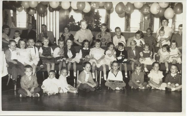 Here it is. The amazing part is that I am in the back row, tallest kid. When I found the photo, I realized that my younger brother is the one holding the plaque SS America. Sailing was in mid 1958. Dan