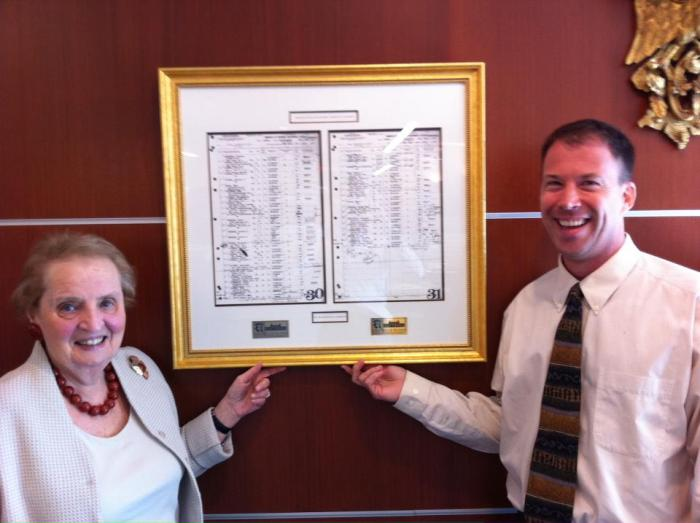 Sec. of State Madeleine Albright and Shali biographer Andrew Marble, standing in front of the manifest for the voyage of the S.S. America, the ship that brought Sec. Albright to the United States from Europe in 1948. Image from Facebook page