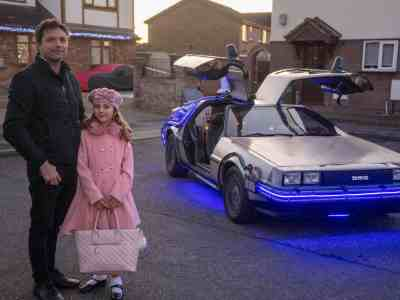 James Napier and his 8-year-old daughter Daisy posing beside their DeLorean.