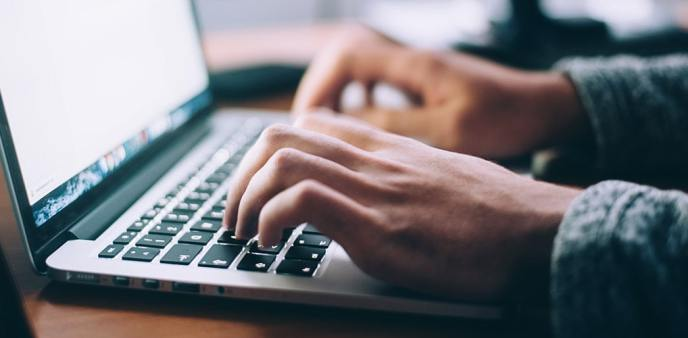 Picture a someone typing their Community Impact Survey Responses on the computer