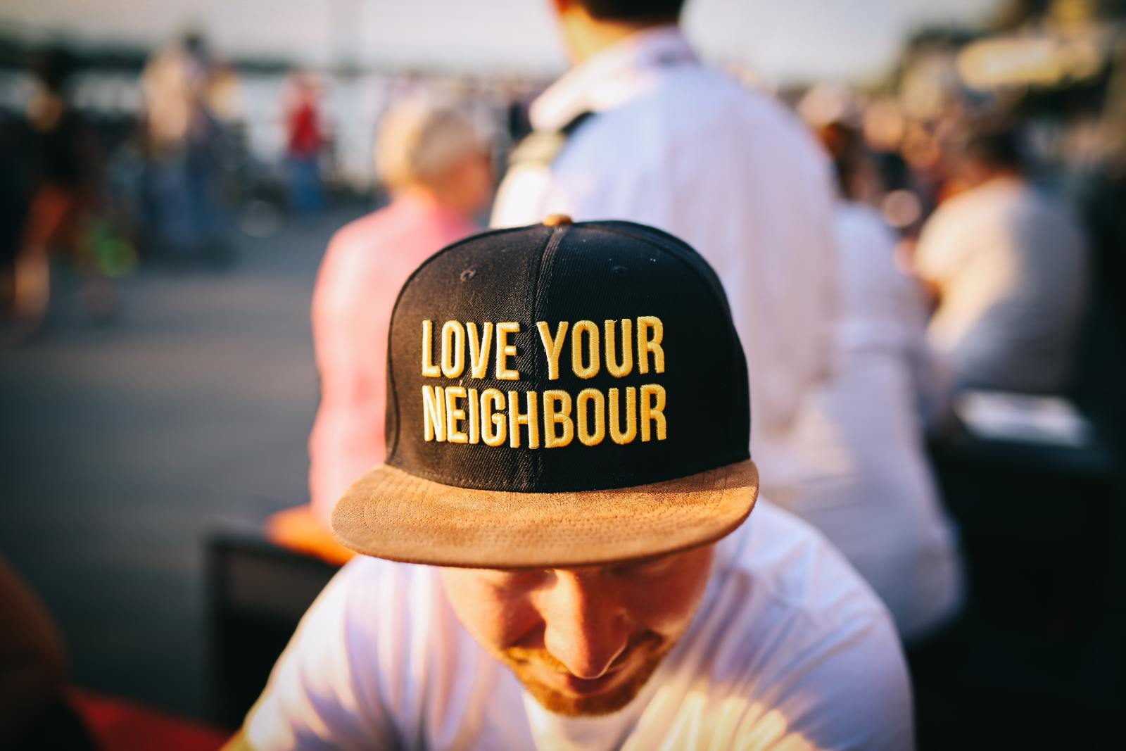 "Picture of a man wearing a hat that says ""Love Your Neighbor"""
