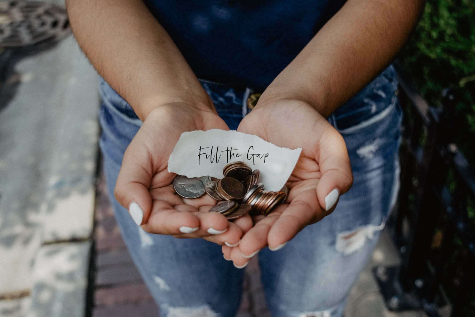 """Girl holding out her hands with coins and a piece of paper that says """"Fill the gap"""""""