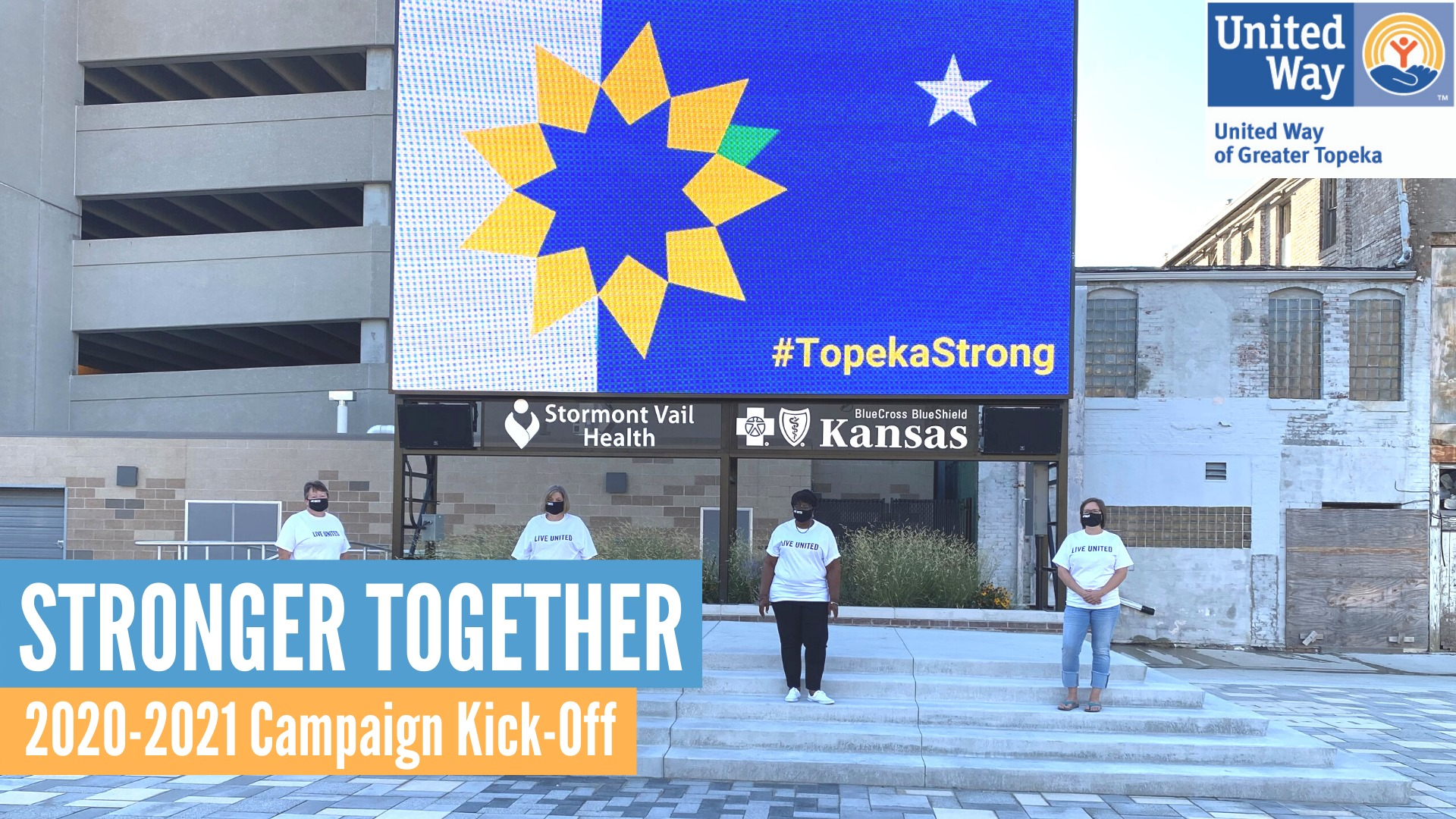 4 Campaign Ambassadors in front of a Topeka flag on the display at Evergy Plaza
