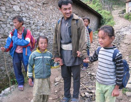 A guardian takes his kids to school in Kathmandu.