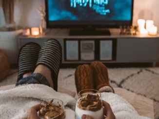 Couple lying on bed watching Harry Potter