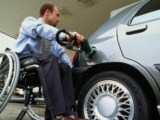 Wheelchair user filling car up at petrol station
