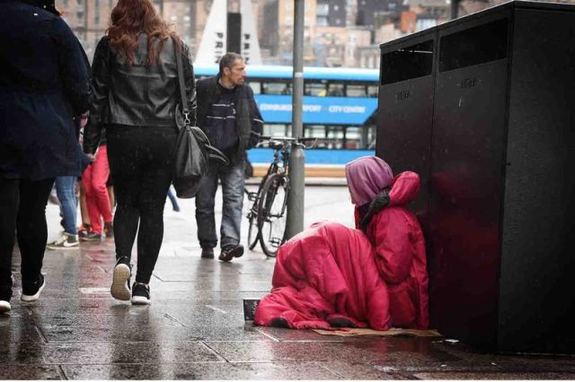 Homeless Person in Sleeping Bag sitting in rain