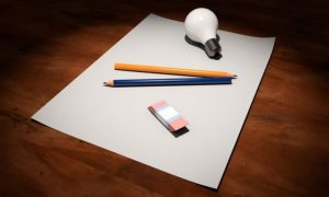 A blank sheet of paper with an eraser, two pencils and a light globe.