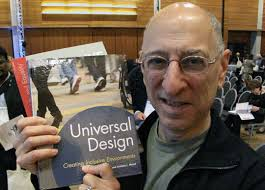 Ed Steinfeld holding his book next to his face. Building accessibility.