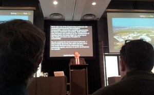 Picture shows a speaker with a live captioning screen behind showing several rows of text.