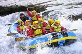 brightly attired people in a semi rigid boat on white water