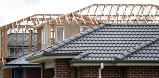 Picture of a grey tiled roof with roof trusses of another house behind