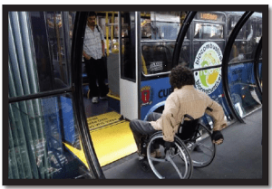 Picture shows a person in a manual wheelchair entering onto the short yellow ramp into the bus from the tube shaped bus shelter