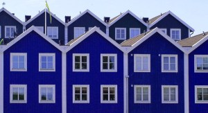 Row of two storey houses, box shape, painted deep blue with white square windows and white bargeboards