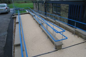 picture showing a zig zag concrete ramp with blue railings