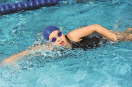 Girl in a swimming race wearing blue cap and goggles