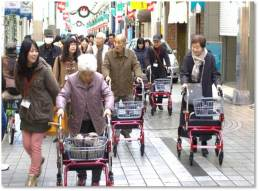 Shows older Japanese people with wheelie walkers on the street