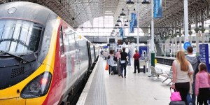 picture of a station platform in the UK with a train standing at the platform and passengers walking