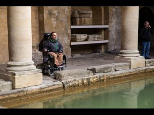 man in a powered wheelchair looking out between Roman columns and across the water in the Roman Bath