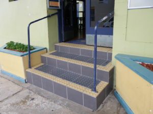 Three steps into a building with tactile markers on every step and a narrow handrail on each side which does not continue to the last step