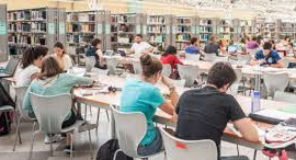 view of university of seville library with students sitting at desks. bookcases are in the background