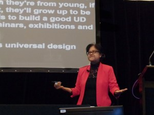 Siam Imm in a bright pink jacket making her presentation on barrier free to universal design Singapore's experience.