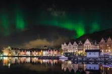 View of a Norwegian waterfront with housing and the Aurora Borealis