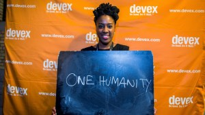 A black woman stands in front of a yellow backdrop with the DEVEX logo. She is holding a blue sheet with the words One Humanity