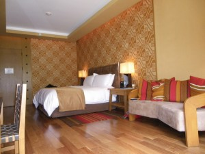 Hotel bedroom with polished floors, orange and red pillows on a couch and textured wallpaper