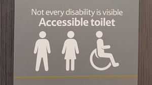 Tesco's accessible toilet sign with additional wording of not every disability is visible