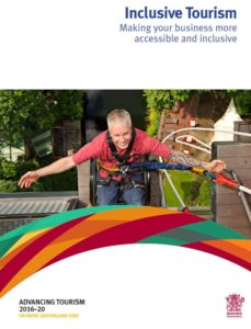 Front cover of Queensland inclusive tourism guide showing a man in a red shirt with his arms outstreched