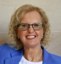 Head and shoulders pic of Jane. She has blonde hair and is wearing glasses, and a bright blue jacket. She is smiling
