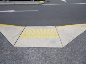 new concrete kerb ramp with yellow tactile indicators