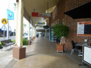 Wide footpath in a shopping strip which has a veranda overhead. There are planter boxes and a seat.